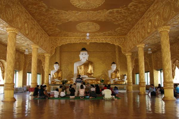 Picture of Buddhists gahtering at the main Buddha statue in the main hall of Shwenokhtaw Pagoda in Pathein