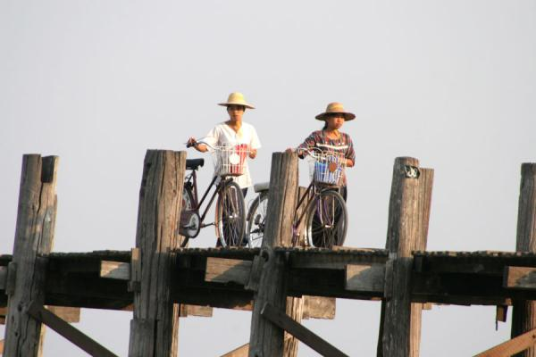 Girls walking their bicycle over U Bein Bridge, Amarapura | Royal Cities | Myanmar (Burma)