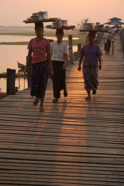 Picture of Women walking their wares across U Bein Bridge at sunset