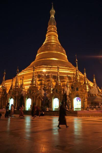 Monk walking past the stupa of Shwedagon Pagoda after sunset | Shwedagon Pagoda | Myanmar (Burma)