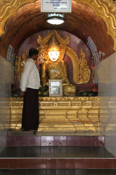 Picture of Snake Pagoda (Paleik) (Myanmar (Burma)): Caretaker of pythons next to the Buddha statue of the Snake Pagoda