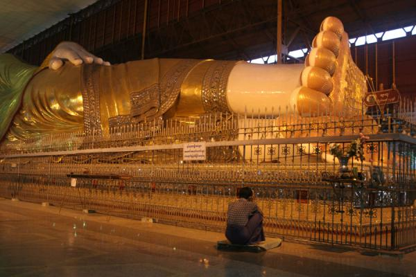 Picture of Devout Buddhist dwarfed by colossal Buddha in Chaukhtatgyi PayaYangon - Myanmar (Burma)