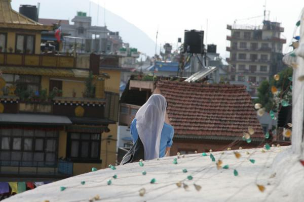 Picture of Boudha Stupa (Nepal): Woman having a quiet moment on Boudha stupa
