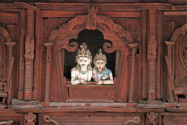 Two statues appearing to look out of a wooden window in the Old Royal Palace | Durbar Square | Nepal