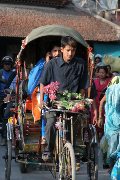 Woman on the phone in bicycle rickshaw | Kathmandu streets | Nepal