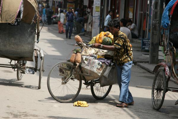 Fruitseller picking up lost bananas from the street | Kathmandu streets | Nepal