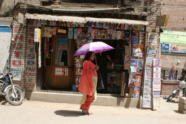 的照片 Woman walking past a shop in Pyaphal Tole - 尼泊尔