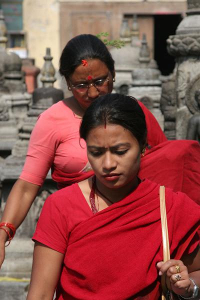 Nepali women in red at Swayambhunath temple | Nepali people | Nepal