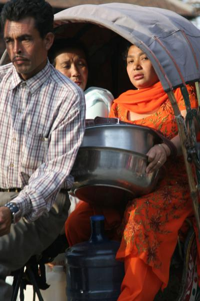 Going home to cook: Nepali woman dressed in orange in bicycle rickshaw | Nepali people | Nepal