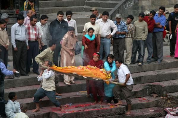 Corpse covered in orange cloth and flowers being lifted to the cremation platform | Pashupatinath Crematie | Nepal