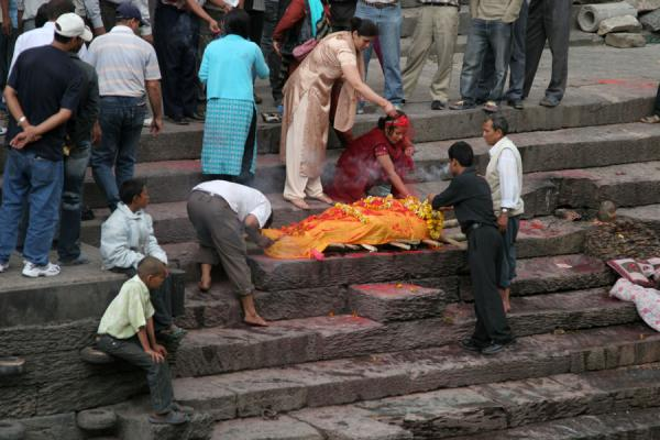 Picture of Relatives cover the corpse, covered in an orange cloth, with white and yellow flowers