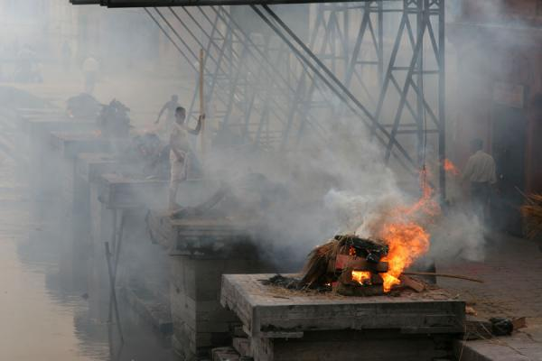 Picture of Burning corpse at Pashupatinath cremation site while someone tries to revive other fire - Nepal - Asia