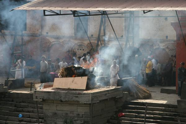 Taking care of the fire of a burning corpse at Pashupatinath | Pashupatinath Crematie | Nepal