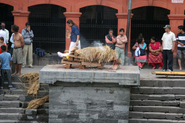 Foto van Smoke starts to billow out of the pyre, the corpse has been covered by strawKathmandu - Nepal