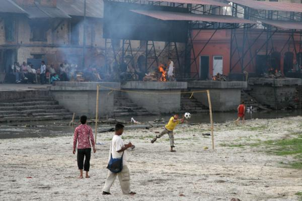 Foto van Boys playing football on the banks of the holy Bagmati river with cremations in the backgroundKathmandu - Nepal