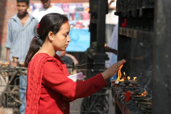 Woman and flame at Swayambhunath temple | Swayambhunath Temple | Nepal