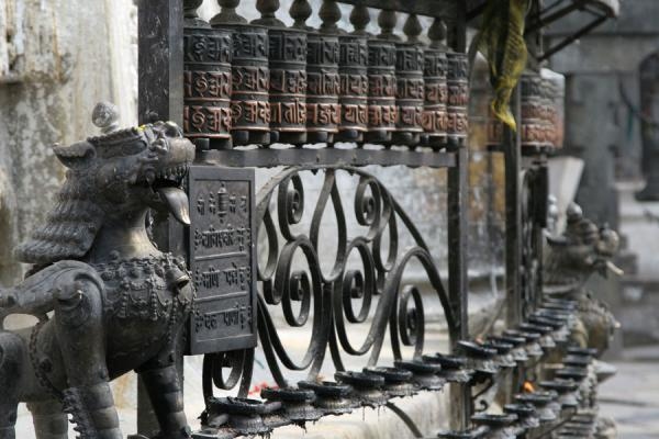 Guardian animal, prayer wheels and candle holders | Swayambhunath Temple | Nepal