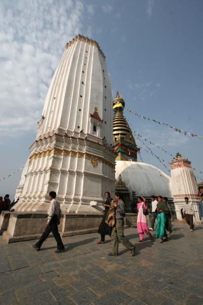 People walking past one of the defining towers of Swayambhunath temple | Swayambhunath Temple | Nepal