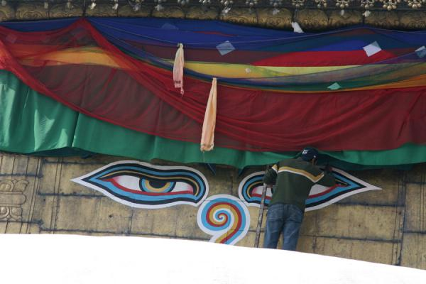 Painting the eyes: painter at work at the top of the stupa of Swayambhunath temple | Swayambhunath Temple | Nepal