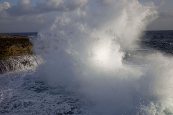 Foto van Wave hurled into the air while crashing on the rocky coast of CuracaoShete Boka - Nederlandse Antillen