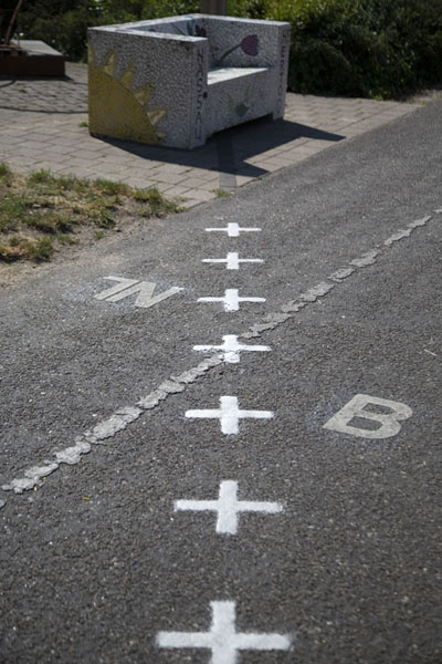 Picture of Border cutting across a cycling path and a benchBaarle - Netherlands