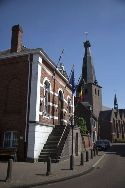 Picture of Street scene in Baarle-Hertog with the former City Hall, currently Heemkundekring, and Saint Remigius church in the background - Netherlands - Europe