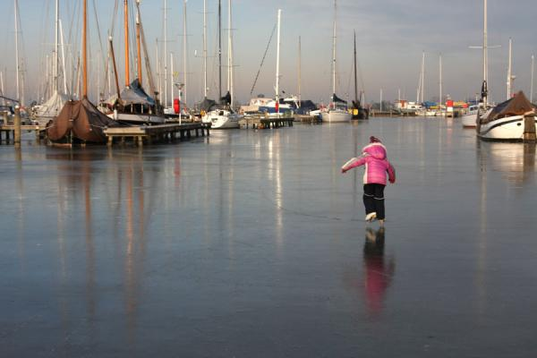 Picture of Natural Ice pastime (Netherlands): Girl skating through the harbour of Monnickendam