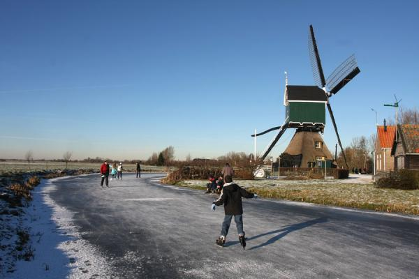 Picture of Natural Ice pastime (Netherlands): Skater and windmill: typical scene near Schoonhoven