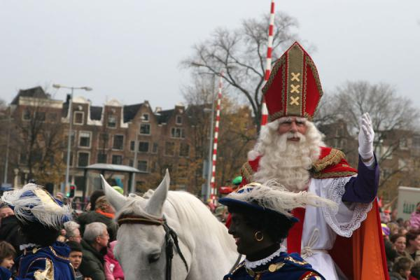 Picture of Sinterklaas on white horse in Amsterdam with the city emblem