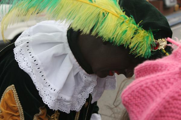Picture of Zwarte Piet talking to a kid during the Sinterklaas parade