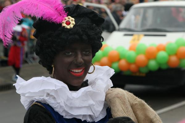 Picture of Zwarte Piet laughing and giving candy away to kids