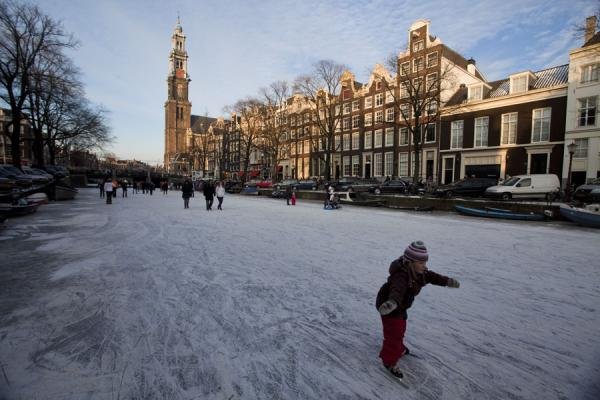 Young girl skating the Prinsengracht with the Westertoren in the background | Schaatsen in Amsterdam | Nederland