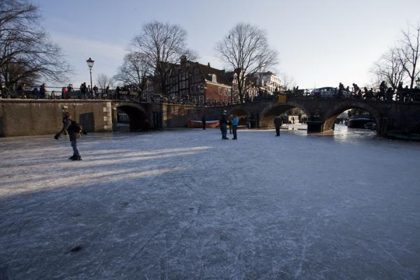 Skaters near a bridge in the Prinsengracht | Schaatsen in Amsterdam | Nederland