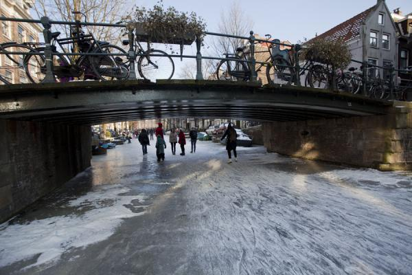 Photo de Passing under a bridge on the frozen ice of an Amsterdam canal - les Pays-Bas - Europe