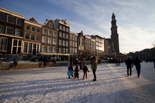 Picture of People enjoying the frozen Prinsengracht with the Westertoren in the background - Netherlands - Europe