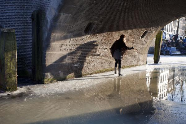 Girl skating next to a hole in the ice under a bridge in Amsterdam | Pattinare sui canali di Amsterdam | Paesi Bassi