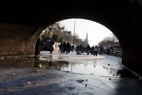 Winter scene framed by an arched bridge at the Prinsengracht | Schaatsen in Amsterdam | Nederland