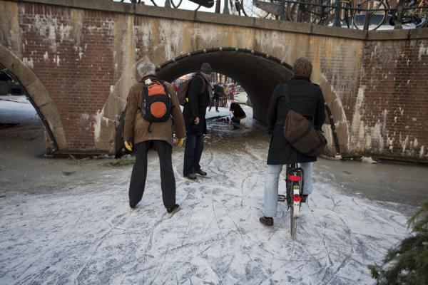 Cycling on the frozen water under a bridge | Patiner sur les canaux de Amsterda | les Pays-Bas