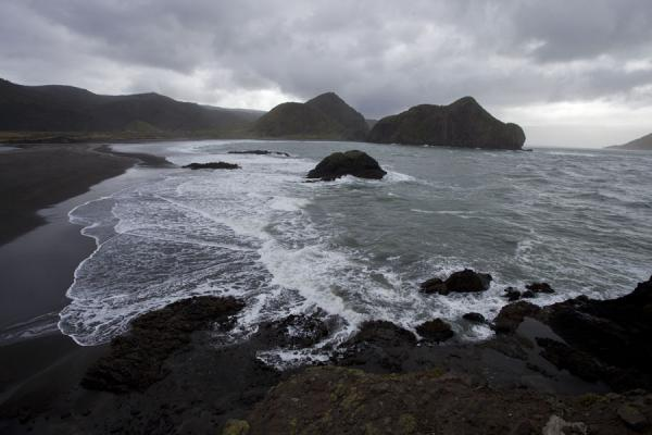 Foto van Nieuw Zeeland (The rugged coastline at Whatipu with waves, rocks, and a black sand beach)