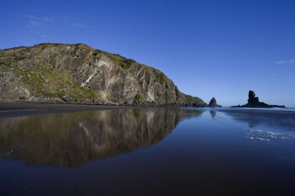 Reflection of rocky cliffs and Keyhole Rock in the black sands of Anawhata beach | Waitakere Ranges Regional Park | New Zealand
