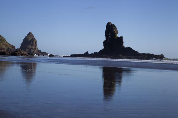 Picture of Waitakere Ranges Regional Park (New Zealand): Keyhole Rock reflected in the black sands of Anawhata beach
