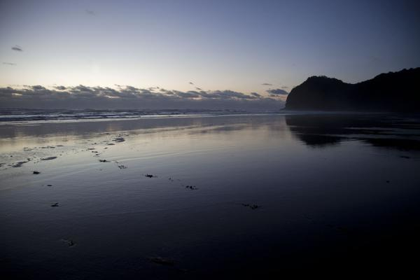 Picture of Waitakere Ranges Regional Park (New Zealand): Reflection of mountain and clouds in the black sands of Piha beach
