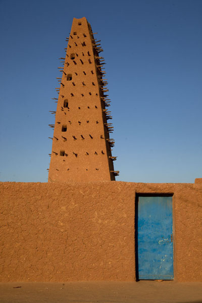 Blue door in adobe wall with the spiked minaret on top | Agadez Big Mosque | Niger