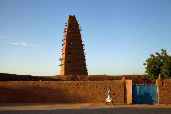 Foto di Man in traditional clothes walking past the Big Mosque of AgadezAgadez - Niger