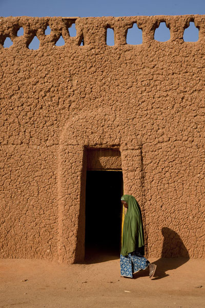 Woman walking past a door in an adobe house in Agadez | Agadez Old Town | Niger