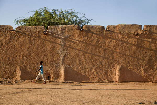Picture of Zinder Old Town (Niger): Adobe wall with boy passing by in front in the Birni quarter of Zinder