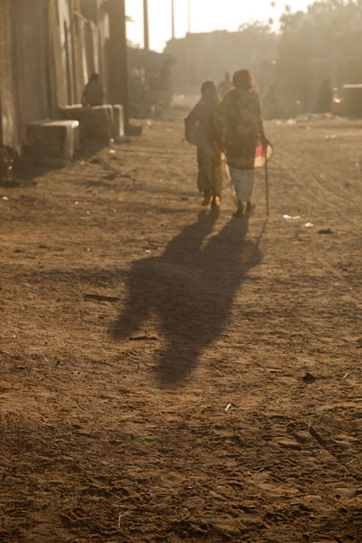 Foto van People walking a dusty street at the end of the day in the Birni quarterZinder - Niger