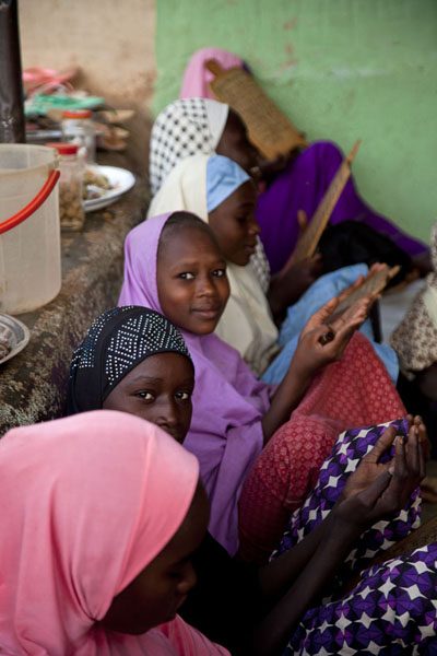 Picture of Zinder Old Town (Niger): Girls with prayer boards secretly looking at the photographer in a madrassa