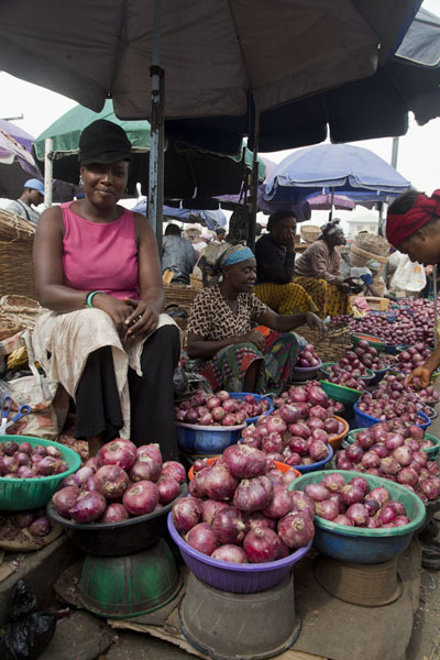 Foto van Stall with onions and cheerful lady at Oyingbo market - Nigeria - Afrika