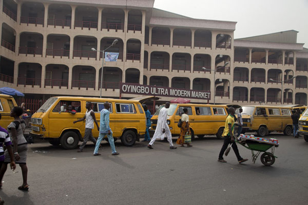 Picture of Street with yellow vans and building of Oyingbo market in the background